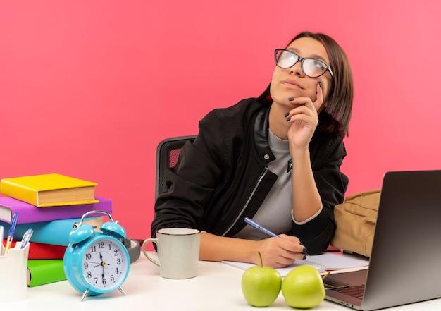 Menina jovem pensativa de óculos, sentada na mesa com ferramentas universitárias, segurando uma caneta, olhando para cima, colocando a mão no queixo, fazendo o dever de casa isolada na parede rosa