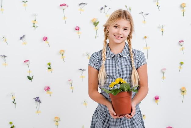 Menina jovem, segurando, pote flores