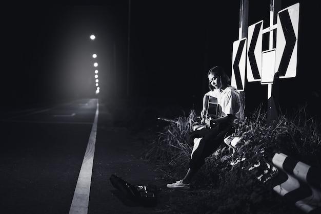 Menina jovem, sentando, e, violão jogo, ligado, estrada, lado, com, sinal estrada, fundo, jornada, de, músico, conceito