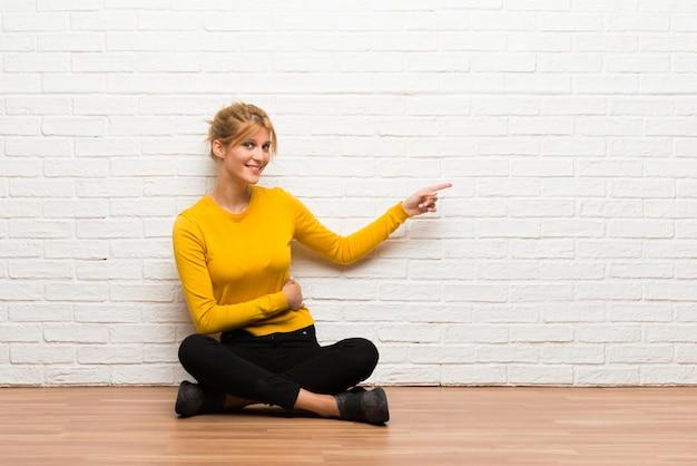 Menina jovem, sentar chão, apontar, dedo, para, a, lado, em, posição lateral