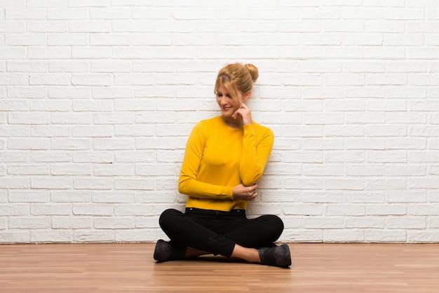 Menina jovem, sentar chão, olhar baixo, com, a, mão, ligado, a, queixo