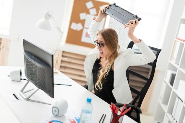 Menina jovem, sentar escrivaninha, em, escritório, olhar, monitor, e, waving, teclado