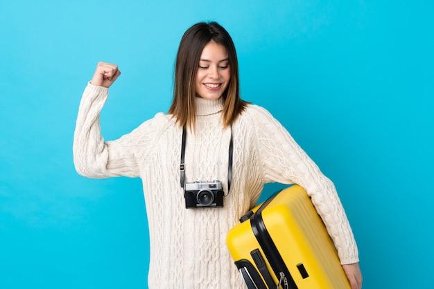 Menina jovem viajante com mala ao longo da parede azul