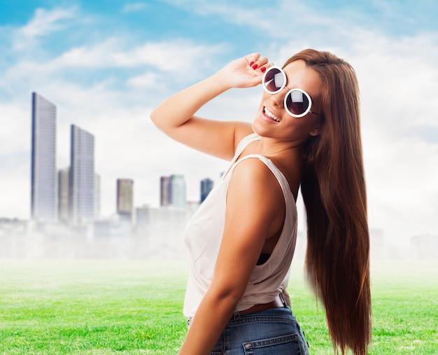 Menina jovial nos óculos de sol de encontro da arquitectura da cidade