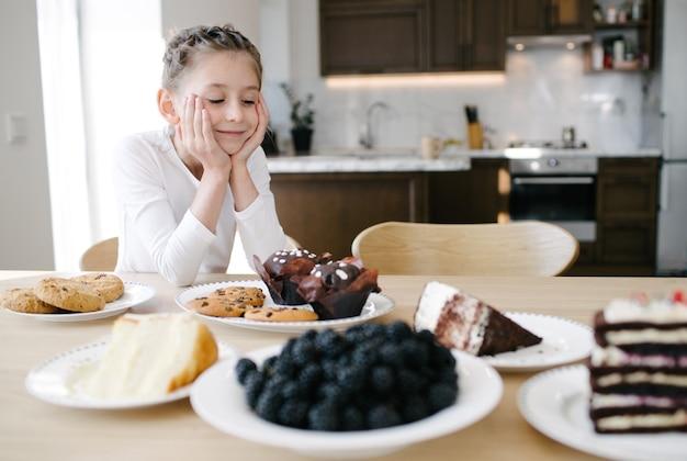 Menina kig sorrindo enquanto olha os bolos em casa