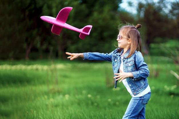 Menina, lança um avião de brinquedo, no ar, jardim ao ar livre