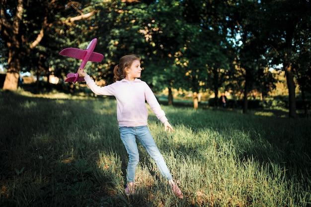 Menina lança um avião de brinquedo no ar no parque
