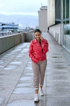 Menina latina com casaco vermelho falando no celular na rua.