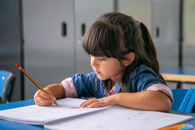 Menina latina de cabelos pensativos sentada na carteira da escola e desenhando em seu caderno