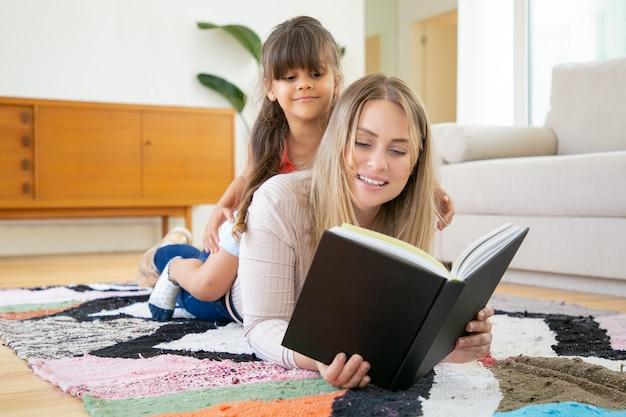 Menina latina sentada nas costas da mãe, sorrindo e olhando para o livro.