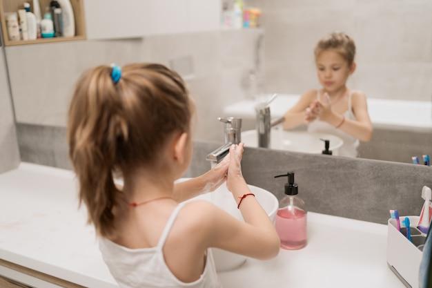 Menina lavando as mãos com sabão
