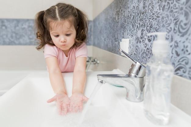 Menina lavando as mãos na pia