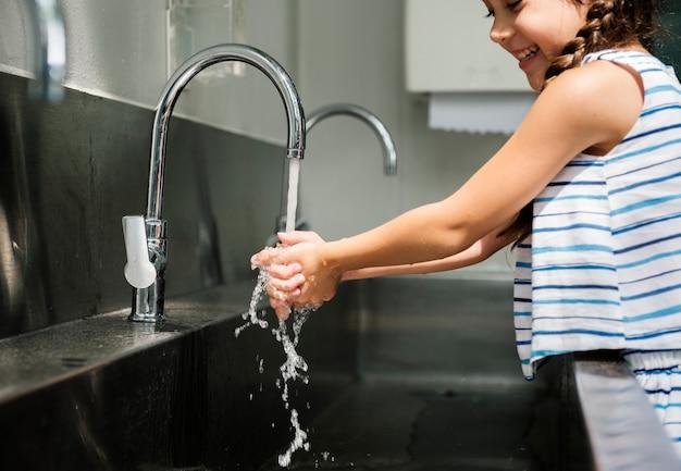 Menina lavando as mãos