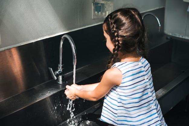 Menina, lavando, dela, mãos