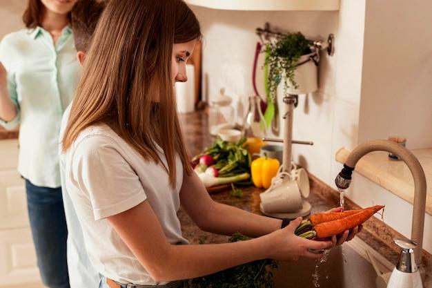 Menina lavando legumes na cozinha, em preparação para o jantar