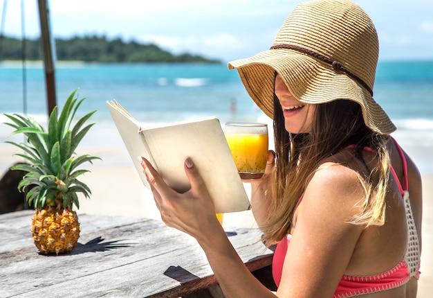 Menina lê um livro à beira-mar