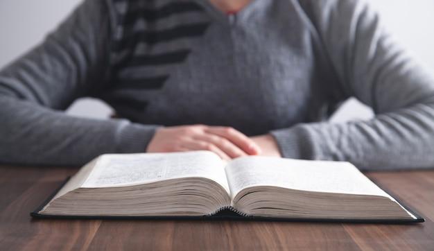 Menina lendo a bíblia sagrada na mesa de madeira.