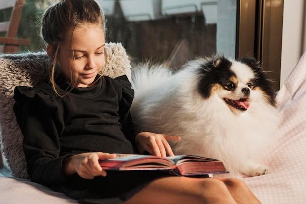 Menina lendo e cachorro ouvindo