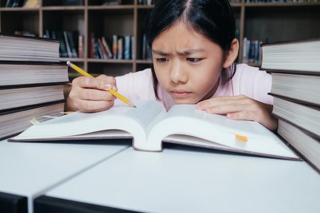 Menina lendo e escrevendo e fazer lição de casa na biblioteca