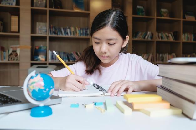 Menina lendo e escrevendo na biblioteca da escola.