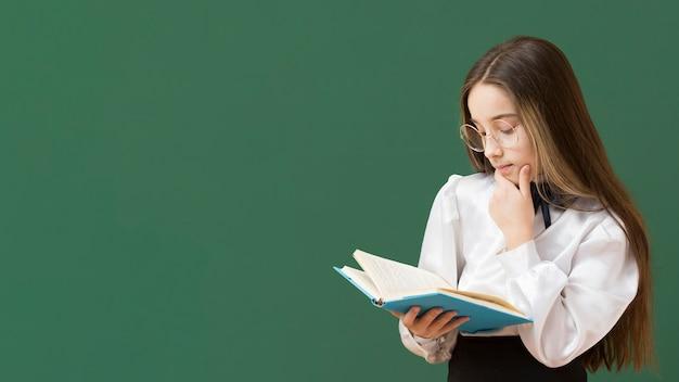 Menina lendo livro cópia espaço