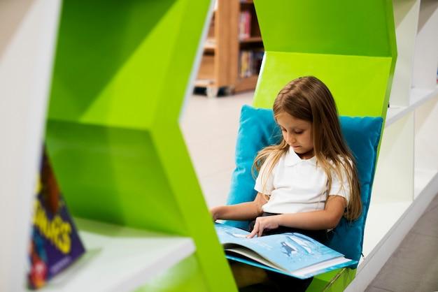 Menina lendo livro na biblioteca da escola