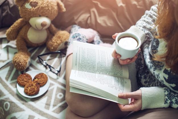 Menina lendo livro na cama com meias quentes, bebendo café