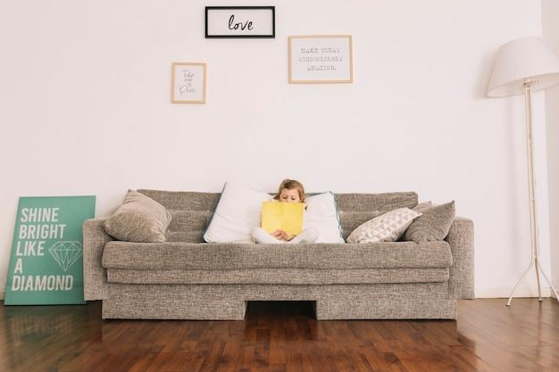 Menina lendo livro no sofá macio
