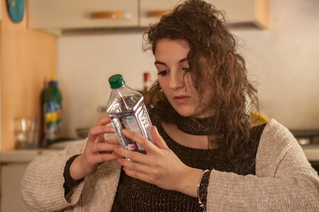 Menina lendo o rótulo da garrafa