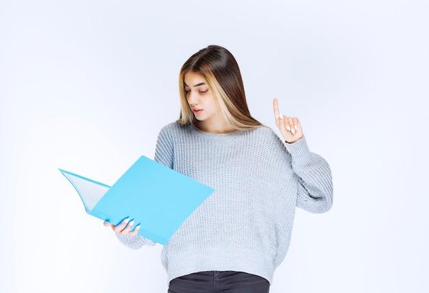 Menina lendo os relatórios na pasta azul e fazendo comentários.