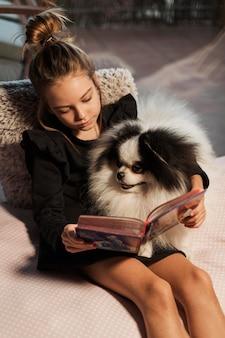 Menina lendo para a visão elevada do cachorrinho branco
