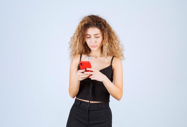Menina lendo suas mensagens no smartphone e parece pensativa.