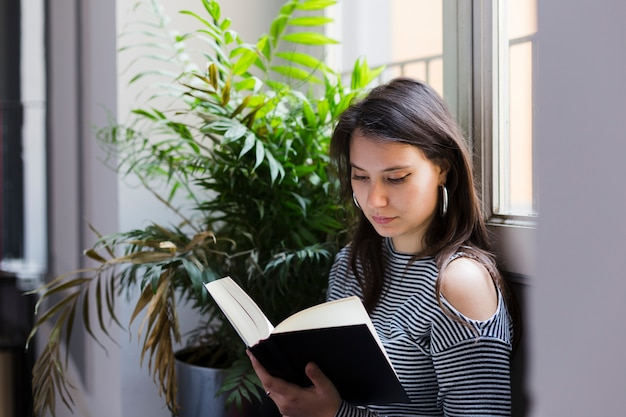 Menina, lendo um livro, casa