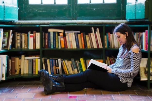 Menina, lendo um livro, chão