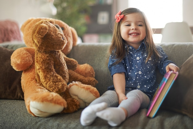 Menina lendo um livro com seus ursinhos de pelúcia