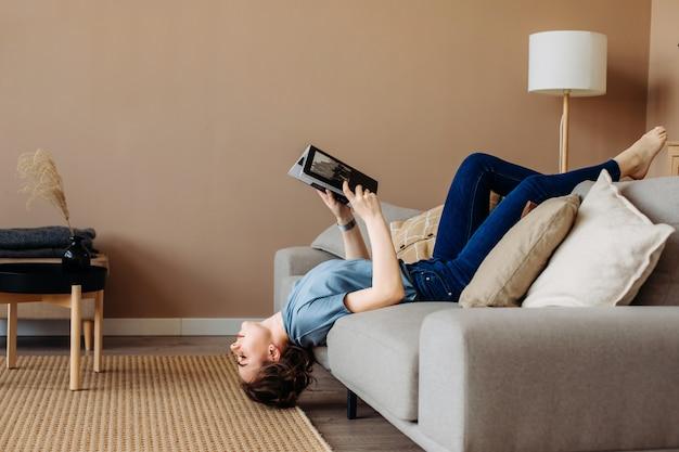 Menina lendo um livro deitado no sofá de cabeça para baixo