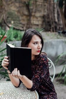 Menina, lendo um livro, em, um, cafeteria