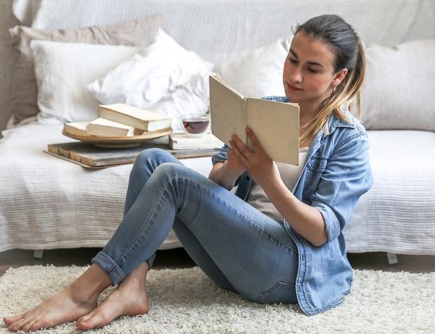 Menina lendo um livro em uma sala aconchegante no sofá com uma xícara de chá, o conceito de lazer e conforto