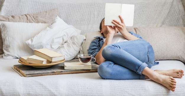 Menina lendo um livro em uma sala aconchegante
