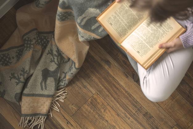 Menina lendo um livro enquanto está sentado na posição de lótus na cadeira na aconchegante sala de estar, conceito de passar o tempo de lazer em casa, foto de fundo do inverno frio