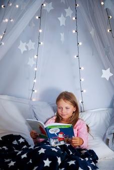 Menina lendo um livro na cama