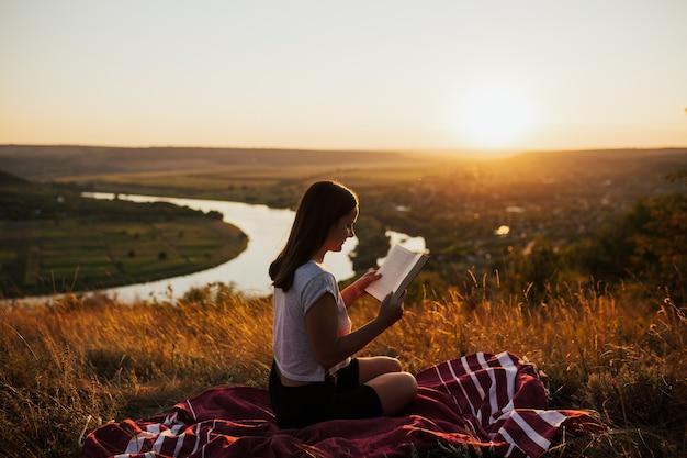 Menina lendo um livro na colina com uma paisagem perfeita, aproveitando o tempo de férias.