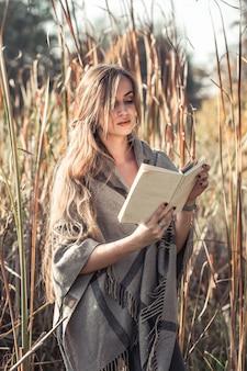 Menina lendo um livro na floresta de outono