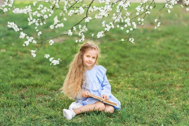 Menina lendo um livro na natureza. jardim florescendo, foto de primavera