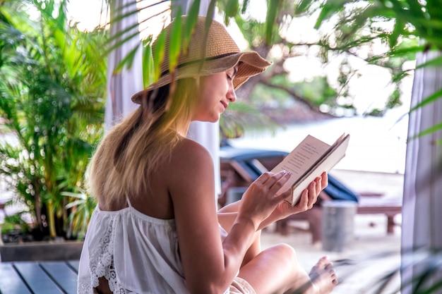 Menina lendo um livro na praia