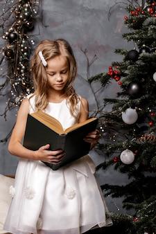 Menina lendo um livro na sala decorada com árvore de natal
