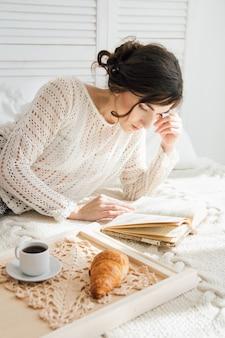 Menina lendo um livro no café da manhã