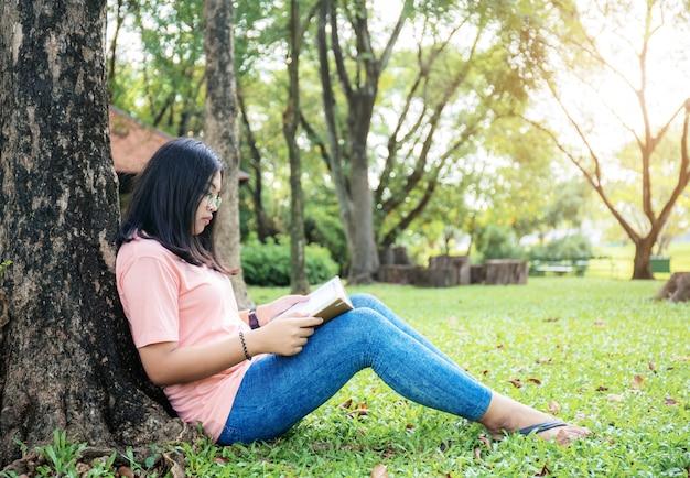 Menina lendo um livro no parque.
