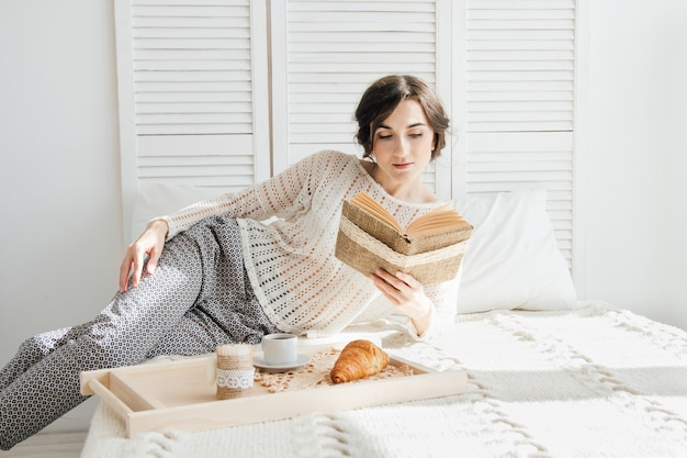 Menina, lendo um livro, pequeno almoço