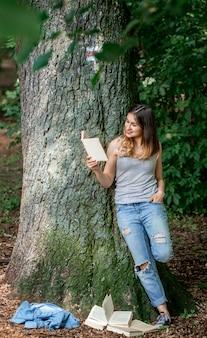 Menina lendo um livro perto de uma árvore no parque
